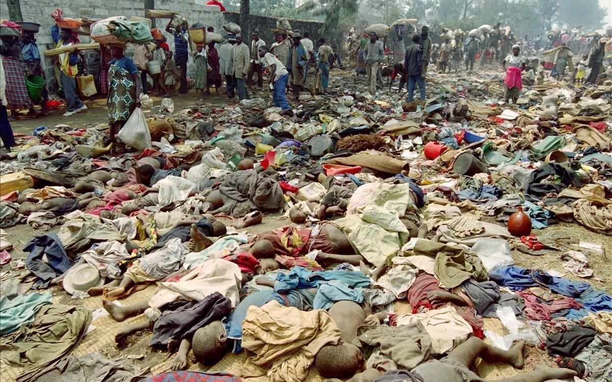 Refugiados ruandeses pasan junto a los cuerpos sin vida de cientos de compatriotas asesinados en la frontera con Zaire el 18 de julio de1994.