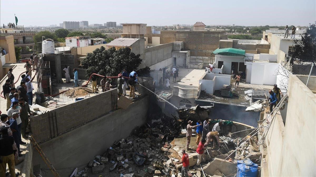 Los equipos de rescate en el lugar de accidente de un avión de Pakistan International Airlines después de que se estrelló en una zona residencial de Karachi.