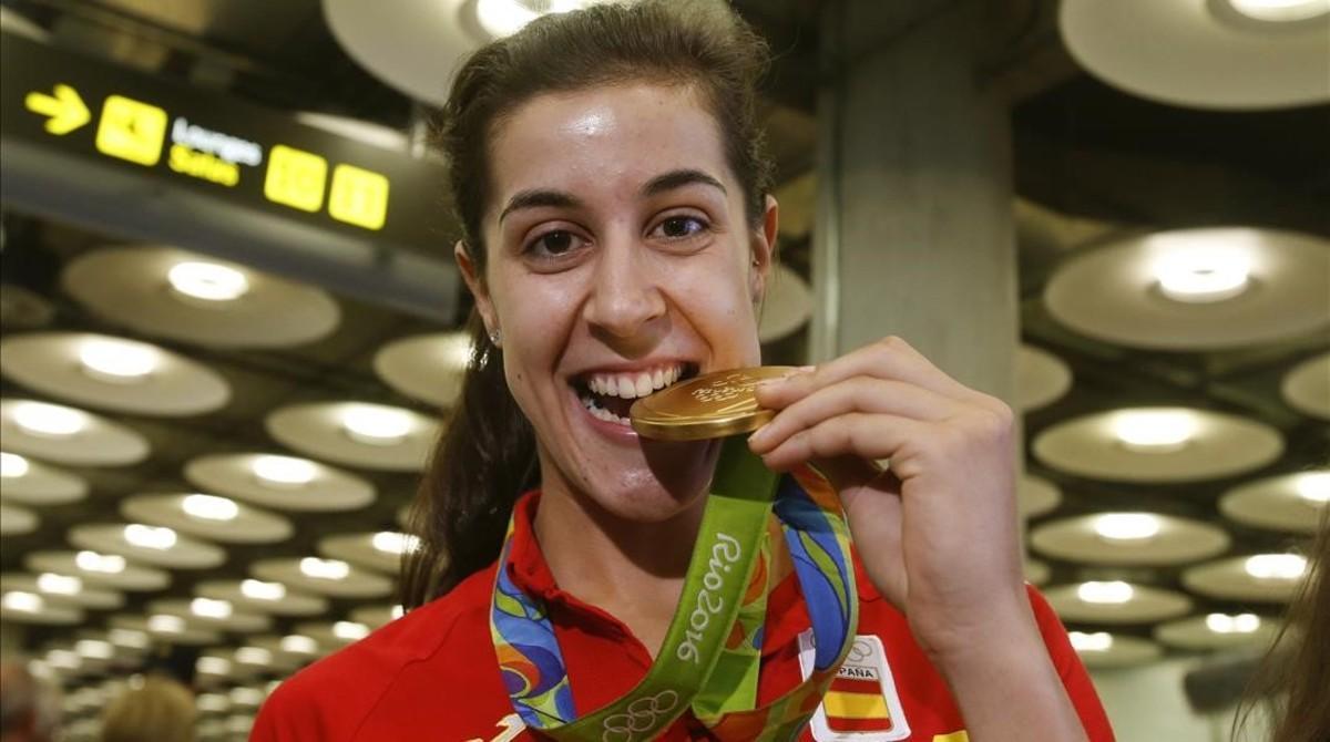 Carolina Marín muerde su medalla de oro en Barajas.