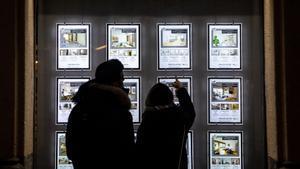 Imagen de unos jóvenes mirando pisos en el escaparate de una inmobiliaria