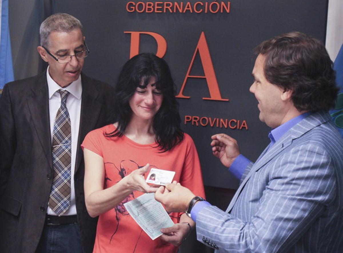 La madre de Luana, Gabriela, recibe el documento de identidad de su hija de manos del jefe de Gabinete del Gobierno provincial de Buenos Aires, Alberto Pérez (derecha), ante el presidente de la comunidad homosexual de Argentina, César Cigliutti.