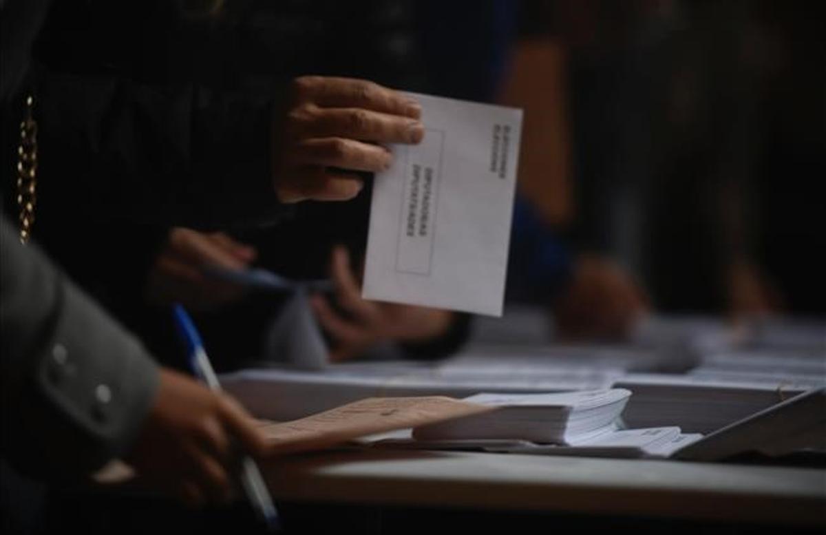 Un elector con su sobre en la mano en un colegio electoral en el 2019.