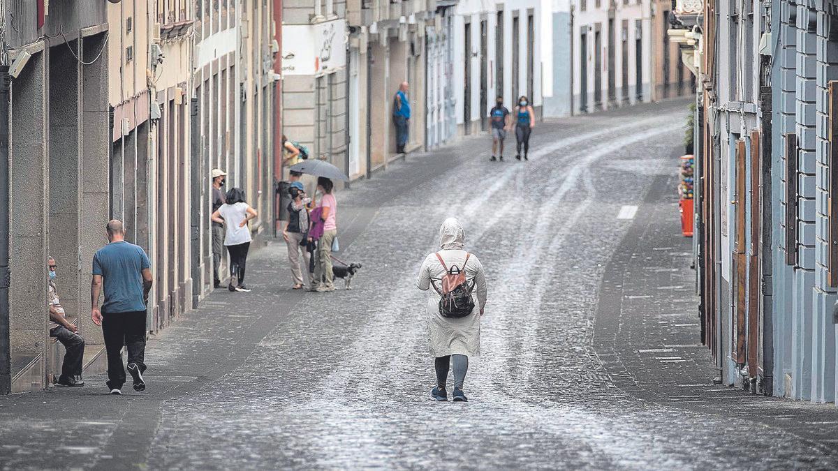 Las calles de Santa Cruz de La Palma cubiertas por un manto de ceniza mientras los palmeros se protegen con paraguas y chubasqueros.
