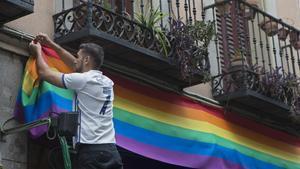 Una persona cuelga una bandera arcoíris en un balcón del barrio madrileño de Chueca.