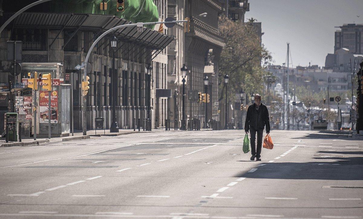 Un hombre regresa de la compra por una Via Laietana completamente vacía por el estado de alarma.