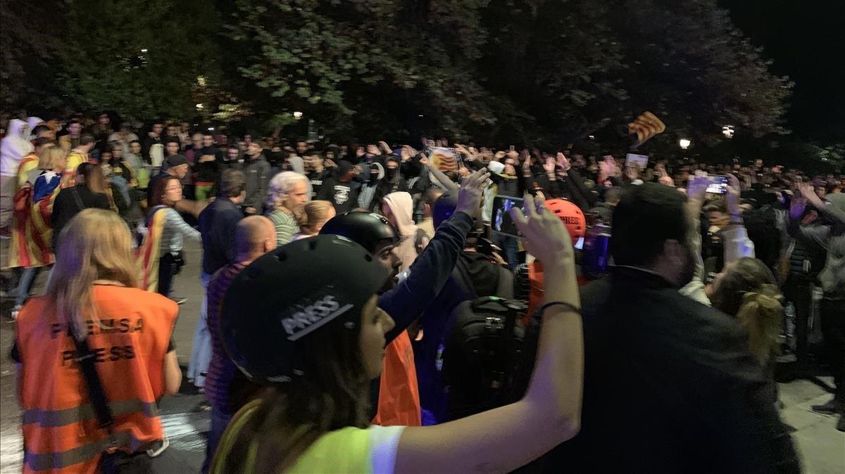 Un grupo de personas hace una barrera entre violentos y la policía en Lleida, este viernes.
