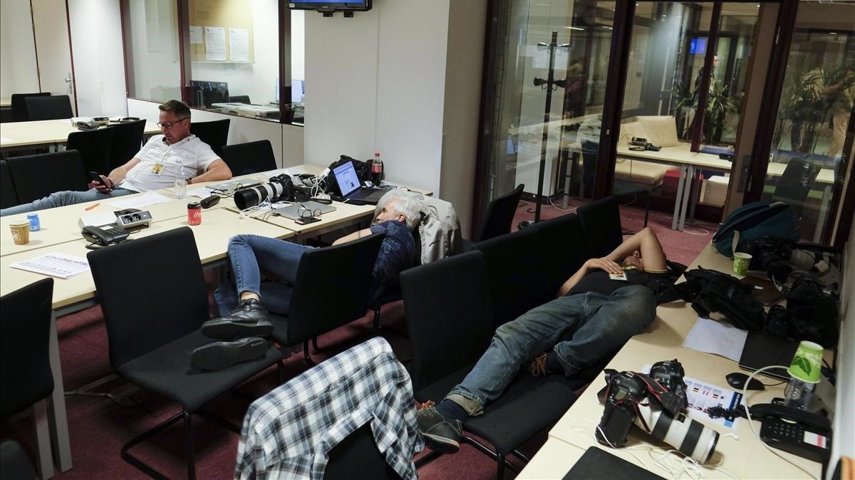 Periodistas descansan esperando el final de la reunión de los líderes europeos en Bruselas.