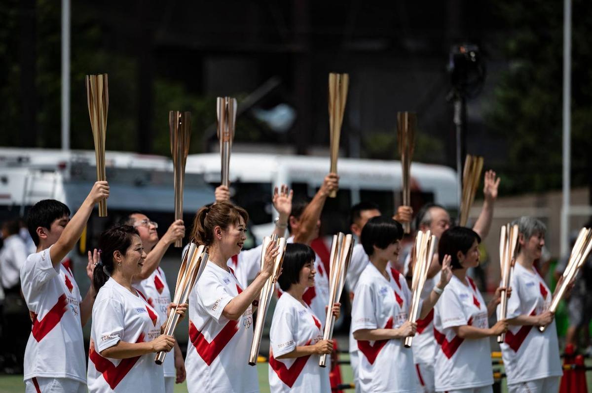 Los relevistas posan con la antorcha olímpica, previo a la apertura de los JJOO.