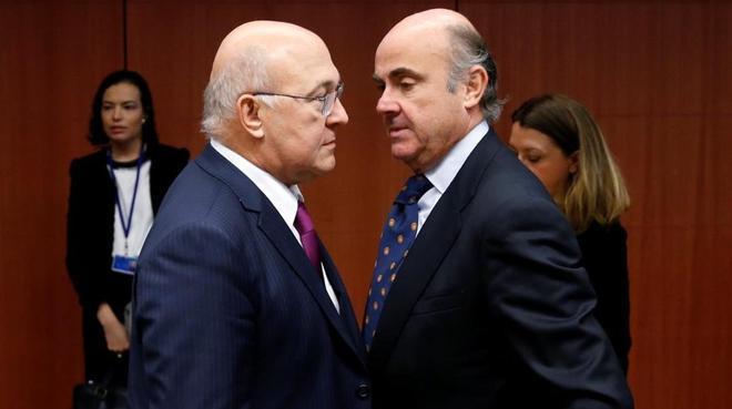 Michel Sapin habla con Luis de Guindos en la reunión del Eurogrupo.