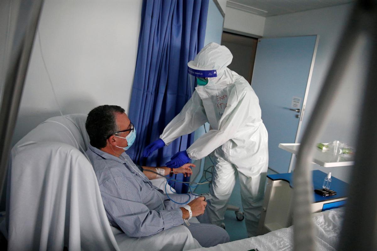 Una enfermera examina a un paciente en la sala COVID del Hospital de Cascais.