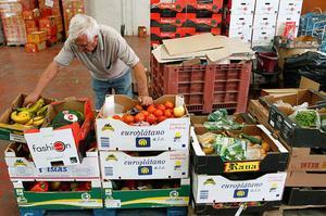 Un voluntari de l'oenagé 'Banc dels Aliments', que té previst distribuir 5 milions de quilograms d'aliments el 2012, a la Pobla de Vallbona (València).