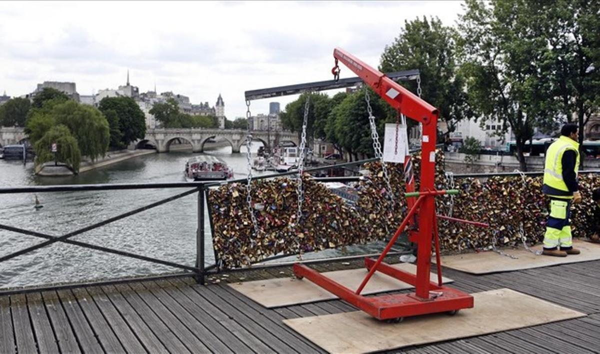 Unos operarios retiran los candados del puente de las Artes con ayuda de grúas.