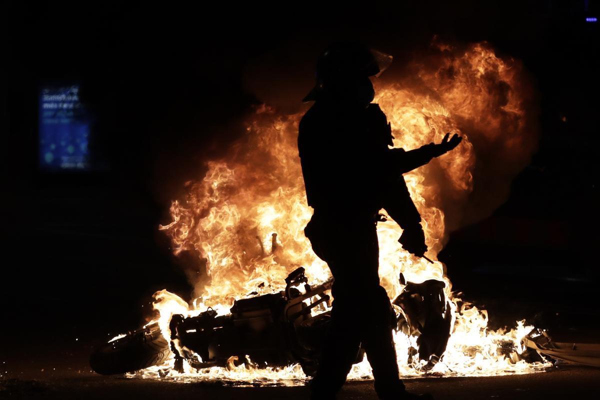 Un mosso d'Esquadra, ante una moto en llamas durante las protestas por la prisión de Pablo Hasél.