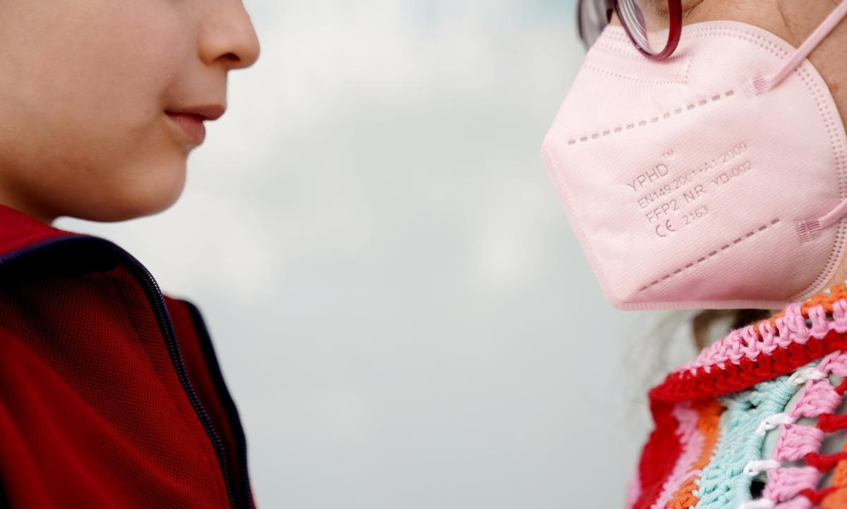 Un niño mira a su madre, que lleva mascarilla, en un parque de Madrid.