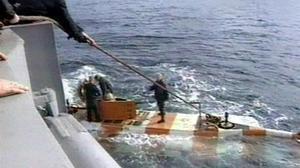 Miembros de los equipos de rescate rusos regresanen un minisubmarinotras una inmersión en busca del sumergible siniestradoen el mar de Barents.