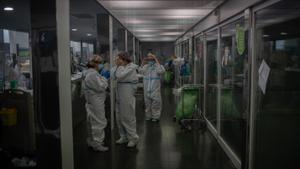 Varios sanitarios protegidos en la Unidad de Cuidados Intensivos -UCI- del Hospital del Mar, en Barcelona.
