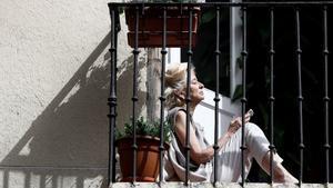Una señora toma el sol en su balcón, en Madrid, durante el confinamiento.
