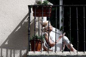 GRA3242 MADRID 19/03/2020.- Una mujer toma el sol en el balcón de su casa en Madrid este jueves durante la cuarta jornada laboral de aislamiento por el coronavirus. EFE/Mariscal