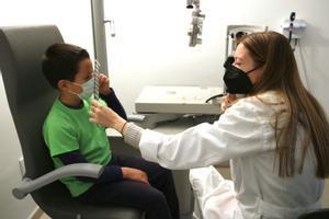 Una estudiante de la facultad de Óptica y Optometría de la UPC Terrassa realiza un test visual a un alumno de la escuela Nova Electra, 2 de marzo 2021