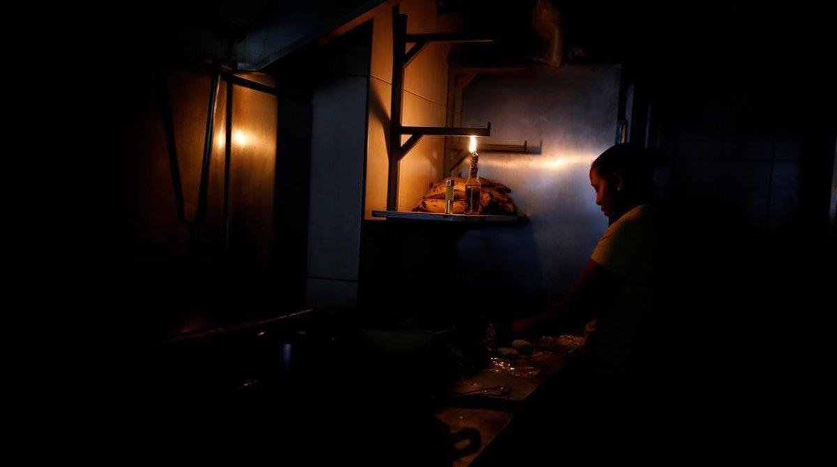 Una mujer usa la luz de una linterna para trabajar en la cocina de un restaurante tras un nuevo apagón en Caracas.