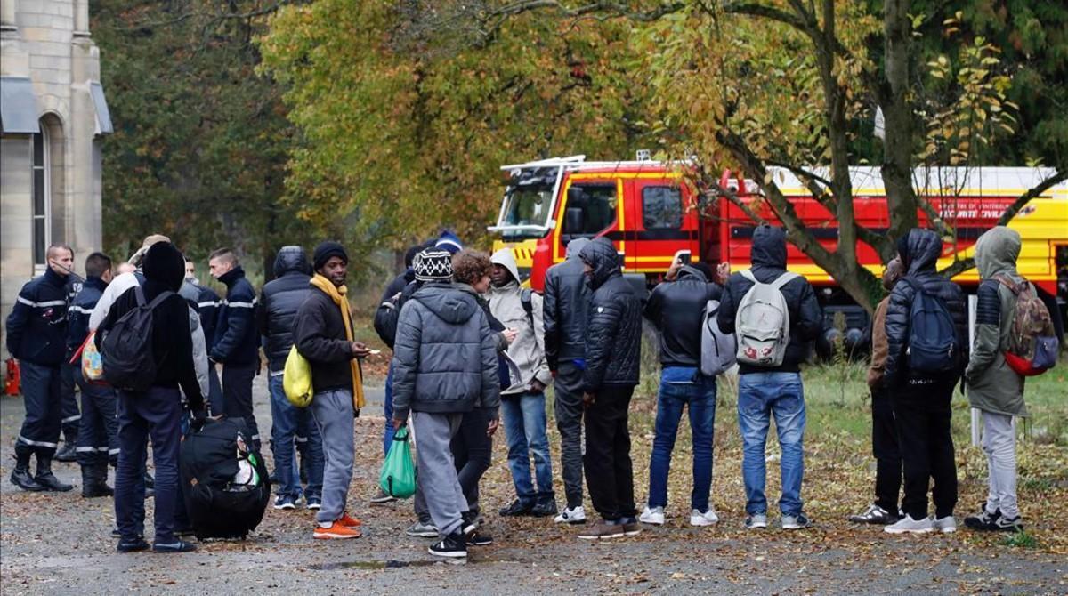 Migrantes acompañados por miembros de la seguridad civil francesa, a su llegada a un nuevo alojamiento en Sarcelles, en el norte de París, este viernes.