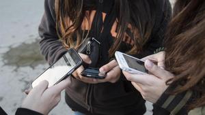 Adolescentescon sus teléfonos móviles.