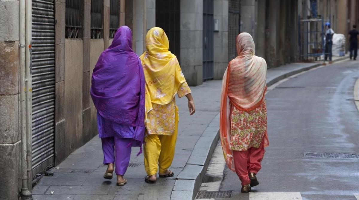 Tres mujeres pasean por el barrio del Raval, en Barcelona.