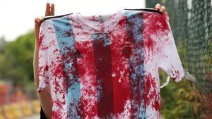 Una mujer Palestina muestra la camiseta de la selección Argentina manchada de sangre en la Ciutat Esportiva Joan Gamper.