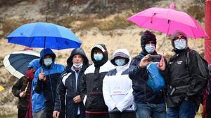 Seguidores del Giro se protegen de la lluvia.