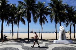 Un hombre pasea en una playa de Río de Janeiro frente a una escultura homenaje a las víctimas del covid.