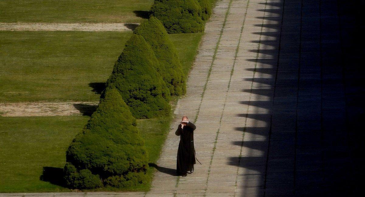 Un fraile caminando bajo la luz cegadora del sol en el Valle de los Caídos.
