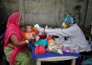 Un médico indio toma la temperatura a un niñoen Ahmedabad, el pasado 15 de junio.