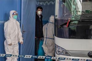 Un miembro de la delegación de la OMS, en el aeropuerto de Wuhan, este jueves.