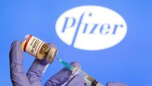 Una mujer sostiene una pequeña botella etiquetada con una etiqueta adhesiva de vacuna contra el coronavirus y una jeringa médica frente al logotipo de Pfizer.