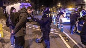 Los agentes de la Guardia Urbana de Barcelona realizan un control de alcoholemia a un conductor de un patinete que circulaba fuera del horario permitido.