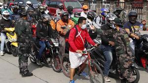 Unos policías toman la temperatura a conductores y motociclistas en Manila, este martes.