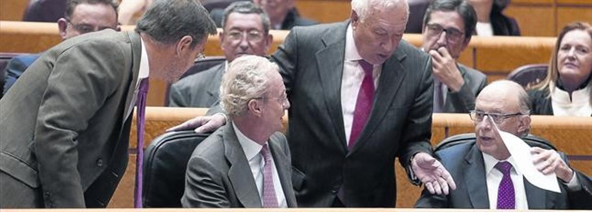 Cristóbal Montoro conversa con los ministros Catalá, Morenés y García Margallo, ayer en el Senado durante la sesión de control al Gobierno.
