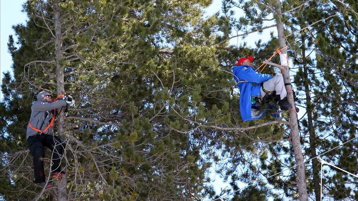 Técnicos de equipos participantes siguen desde unos árboles la evolucion de sus esquiadores.