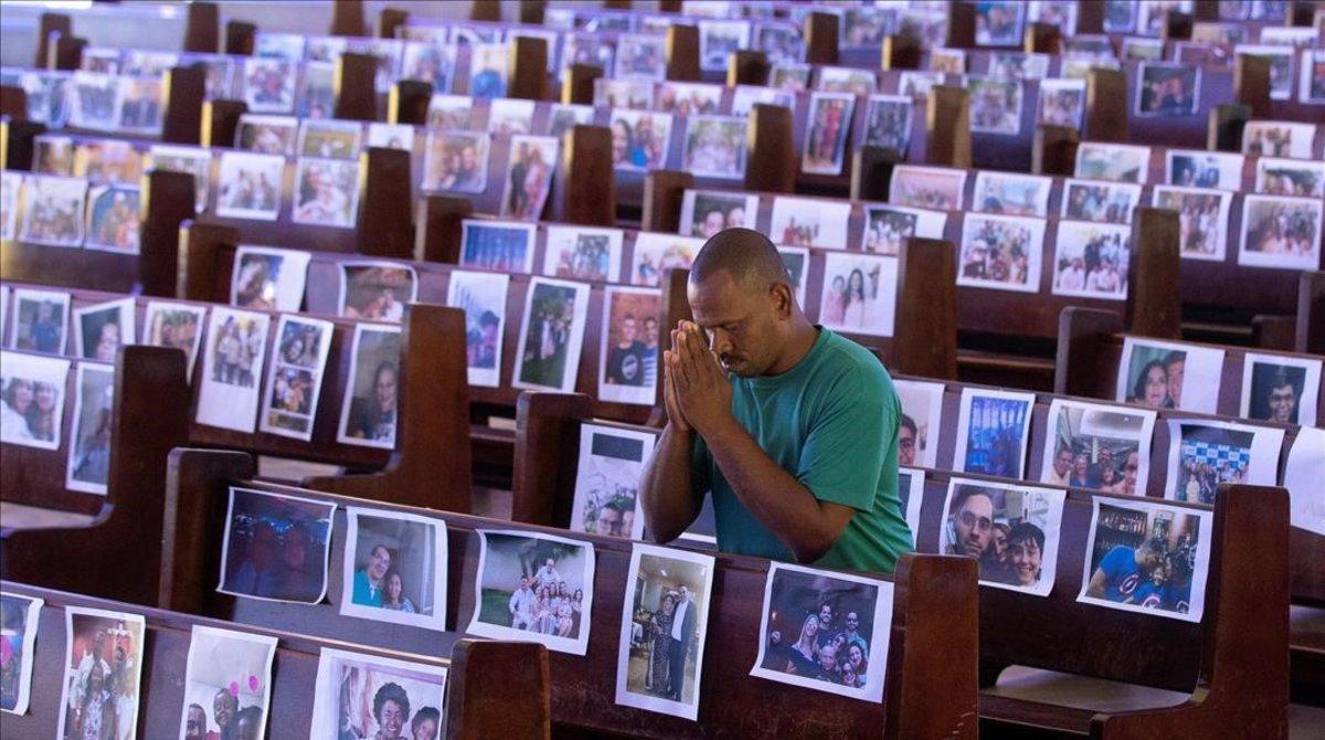 Un hombre reza el jueves santo en una iglesia de Brasilia, Brasil, en la que colocaron fotos de feligreses en los bancos vacíos.