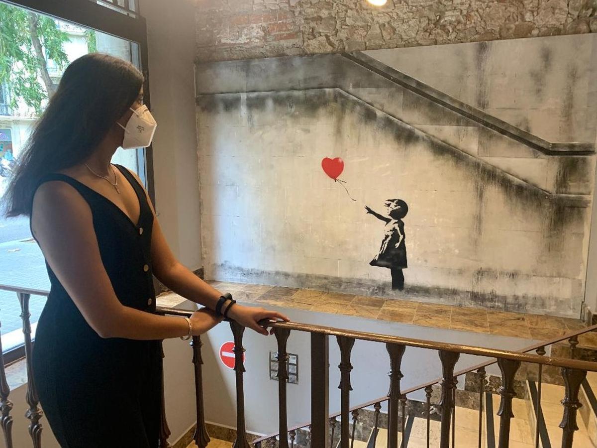 Una mujer contempla la famosa imagen de la niña con el globo.