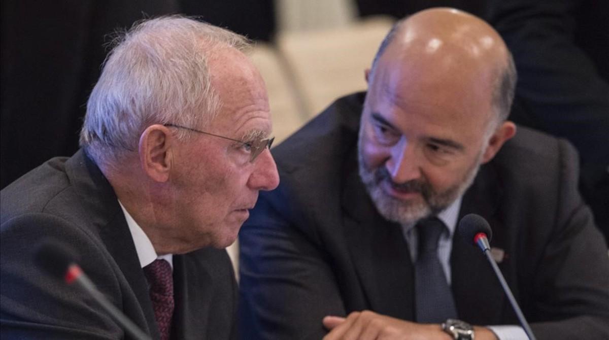 El ministro de Finanzas alemán, Wolfgang Schauble, conversa con el comisario europeo de Asuntos Economicos y Financieros,Pierre Moscovici,durante la reunion de los ministros de Economia y Finanzas de la zona de euro en Bratislava.