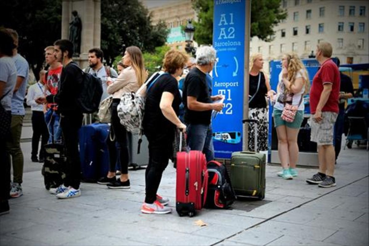 Varios turistas esperan el autobús al aeropuerto en la plaza de Catalunya.