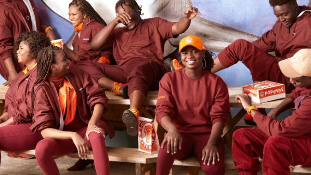 Empleados de Popeyes Chiken lucen los uniformes de la cadena de comida rápida.