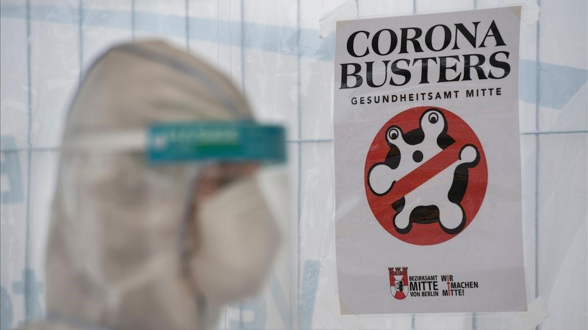 Un sanitario con equipo de protección y máscara junto a un cartel de Corona Busters colgado en un hospital de Berlín
