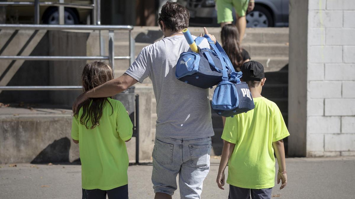 Un padre carga con las bolsas de deporte de sus hijos, en un club deportivo de Barcelona