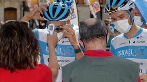Ciclistas del equipo israelí Start pasan el control de temperatura antes de la salida