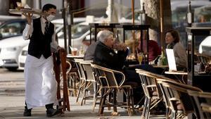 Un camarero trabaja en la terraza de un bar abierto en Madrid.