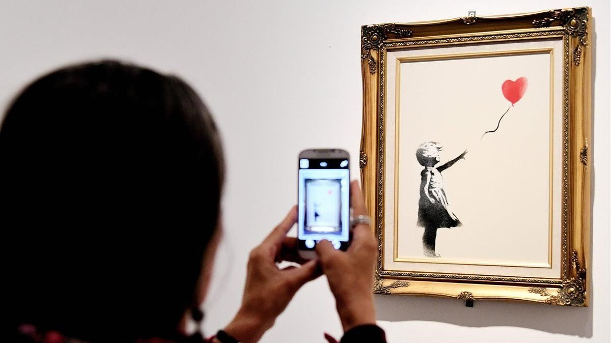 Una mujer toma una foto del lienzo'La chica con globo'.