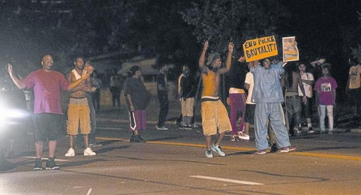 Un grupo de manifestantes protestan por el asesinato de Michael Brown en una calle de Ferguson, en el estado de Misuri, ayer.