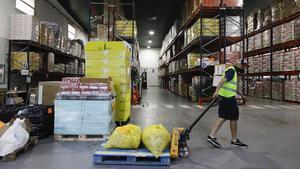 Un operario traslada comida en el almacén del Banco de Alimentos de Barcelona.